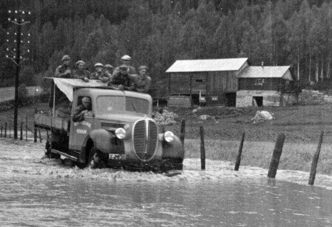 Ein lastebil frå Kvam fossar gjennom flomvatnet i Vika mellom Kvam og Vinstra. Jernbanesporet ligg godt under vatn. Med så mange staute karar på lasteplanen er det vel rimeleg å tru at dei er ute på oppdrag i samband med flommen.