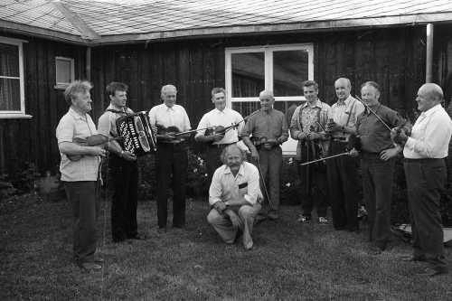 Gamle Fron spelemannslag i 1972.  Frå venstre: Harald Haug (Vågå), Arne Vangen (Harpefoss), Ragnar Fosse (Skåbu), Paul Brenna (Ruste), Paul Brenden (Skåbu), ukjent, Ola Morken (Ruste), Arne Risdal (Skåbu), Ivar Fosse (Skåbu) og i midten fremst, Hans Petter Kleiven (Vinstra). Bildet er teke utanfor Vinstra vidaregåande, truleg i samband Peer Gynt-stemnet. Dette året var det ingen aktivitet i Vågå spelemannslag, og det var derfor Harald Haug var med.