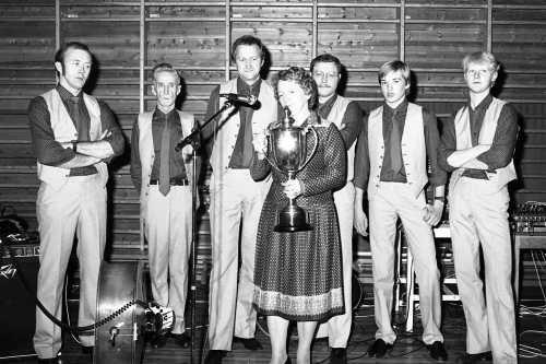 Karlsrud og Nermoen Gåmmåldansorkester vann NM i gammaldans i 1984. Frå venstre: Konrad Havn (kontrabass), Pål Karlsrud (trekkspel), Ivar Nermoen (trekkspel), Hans Bergum (gitar), Øystein Rudi (fele) og Erik Bjørke (fele). Signe Morken står med pokalen og held tale til vinnarane.