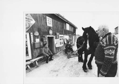 """Heide-butikken; Eit kjent landemerke i Skåbu som dessverrre høyrer til svunne tider. Den gamle Heide-butikken eller """"Timannbua"""" som det vart sagt på folkemunne, blei fyrst totalskadd i brann. Den vart bygt opp att og seinare nedlagt (rundt 1980). Bua vart vidkjent for rakefisken sin. Til høgre Timann Heide, på benken sit sonen Kristian og på sleden ser vi Ola Dalen. Her var """"Reirin""""* innom både titt og ofte for å handle og slå av ein prat. I midtre delen var det kafé og dette vart ein viktig sosial arena for folk i Skåbu. Her var det nok ikkje langt imellom gode replikkar og artige historier! Anton vart teke godt vare på og fekk mykje hjelp av Timann og Kristian. I takksemd for dette utparsellerte han ei hyttetomt frå eigedommen sin som han gav Kristian. Somme gonger hadde han også med seg fersk kokefisk til Heide-karane. Biletet er teke rundt 1970. Utlånt av Marie Heide."""