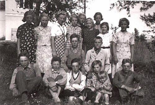 Arne Risdal som konfirmant i Skåbu i 1938. Fremst frå venstre: Jens Sæther, Arne Risdal, Trygve Veslum, Håkon Hage med Kari Hernæs på fanget, Ola Grosberghaugen. I midten: Ivar Berget og Ivar Kappelslåen. Bak frå venstre: Olga Syverhuset (Smikop), Kristine Været (Smikop), Bertha Kampeseter (Kristiansen), Maria Blekastad (Slåen), Astrid Sande (Steine), Camilla Andresen, Gudrun Askheim, Kristine Heide (Risdal) og Signe Øvre Fosse (Tårud). Bildet er tatt nord for skulehuset i Skåbu